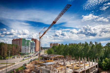 Gru della costruzione e costruzione in costruzione contro il cielo blu