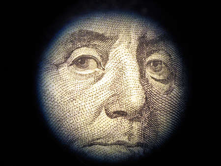 falsity: Close-up of Benjamin Franklin, one hundred dollars note. The financial inspector checks falsity