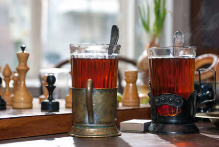 Two glasses of tea in old cupholders on a wooden table next to the chessboard near the window