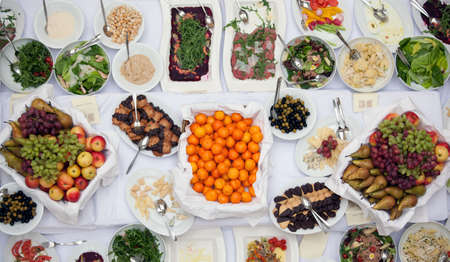 Top view of plates with delicious homemade food , garden berries, fruits, cups and Cutlery on the big table