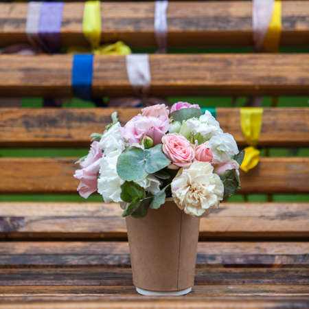 Small bouquet of flowers on a wooden bench