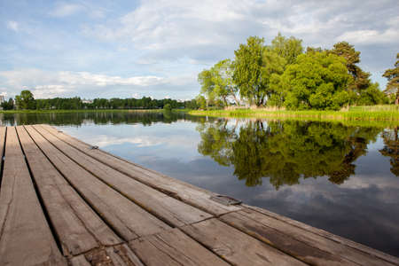 View from the dock to the water and green forest Stock Photo