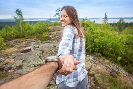 De de holdingsmens van de toeristenvrouw door de hand en het lopen onderaan de bergvallei kijkt en glimlacht bij de camera