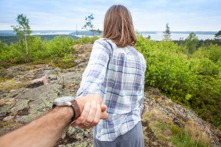 Toeristische vrouw man aan de hand te houden en lopen de bergvallei