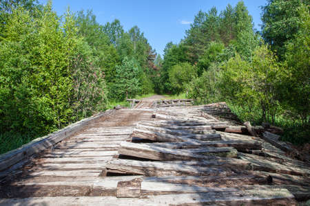 Old ruined wooden bridge on a dirt road in the forest