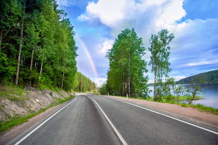 highway near the lake and forest. on the horizon rainbow Stock Photo