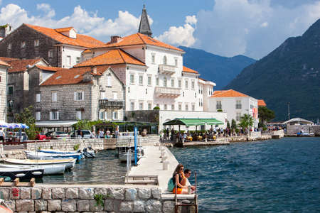 PERAST. MONTENEGRO - September 2018. Beautiful View ancient city of Perast is located in Boka Kotorska Bay of the Adriatic sea on Sunny summer day. Tourists walk along the promenade of Perast