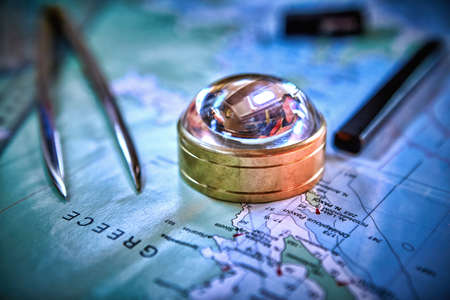 Magnetic compass and magnifying glass on map