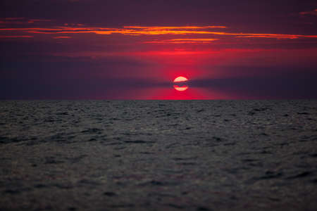 Beautiful red and orange sunset over the sea in a cloudy sky. The sun goes down over the sea. Two seagulls are flying against the sunset. Dramatic Sunset Sky Фото со стока