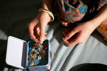 Woman at home examines a beautiful decoration in a jewelry box, hands close-up 版權商用圖片