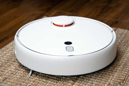 Robotic vacuum cleaner cleans the room from dust and debris, technological progress. Reklamní fotografie