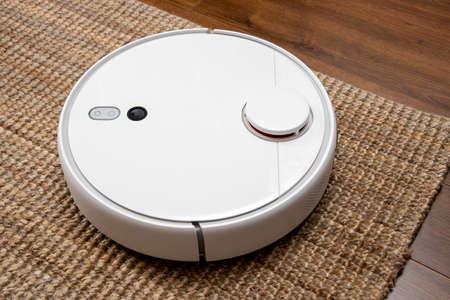 Robotic vacuum cleaner cleans the room from dust and debris, technological progress. Фото со стока