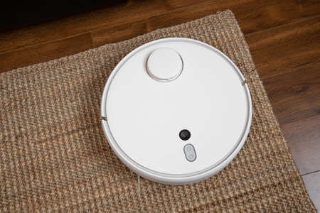 White robotic vacuum cleaner on laminate floor cleaning dust in living room interior. Smart electronic housekeeping technology.