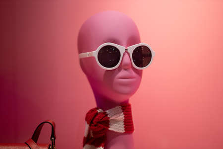 mannequin of a woman with white glasses on a pink background