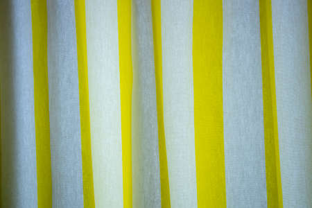 Creased striped yellow and white cloth material fragment as a background. the curtain in the room