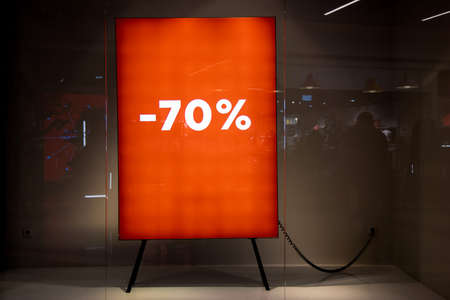70 Percent Bright Red Sale Background with glowing numbers. window with space for text.Sign in a clothing store with discount inscription