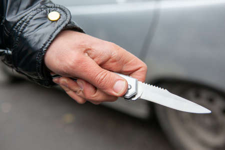 Folding knife in the hand of the criminal close-up. a man in a black jacket Фото со стока