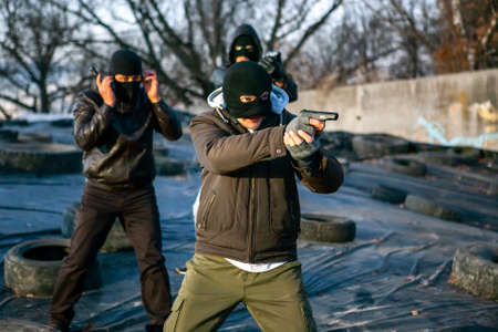 Male criminals, gangsters wearing masks and guns in a disadvantaged area of the city