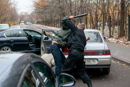 Men fight after a car accident on the road Фото со стока