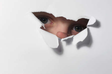 Two childrens eyes with a paper hole through it.
