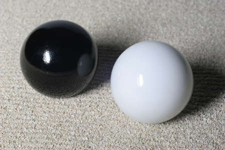A white and a black ball lay in the sand. photo
