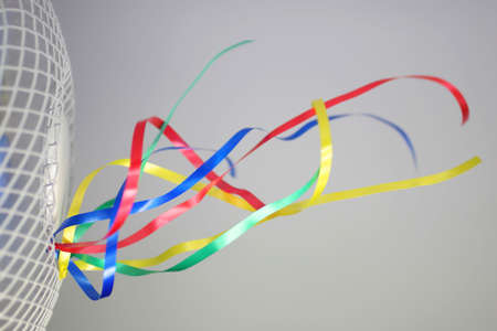 Colorful ribbons fluttering in the air stream of a fan. Stock Photo