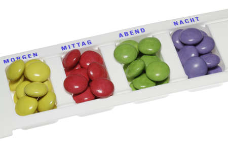 Colorful tablets are sorted by time of day in a box. photo
