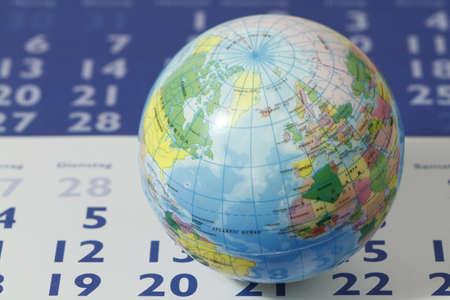 A small globe lies on a calendar sheet. photo