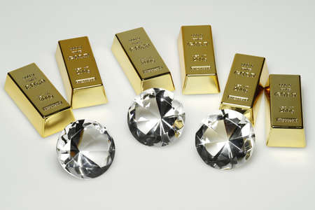 Gold bars and diamonds are together on the picture. Standard-Bild