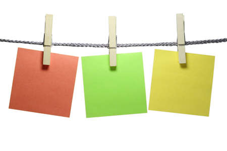 At a cord hanging three clothespins with a sticky note. Banco de Imagens