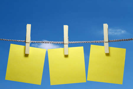 At a cord hanging three clothespins with a sticky note. photo