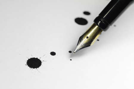 A pen has ink blots sprayed onto a sheet of white paper.