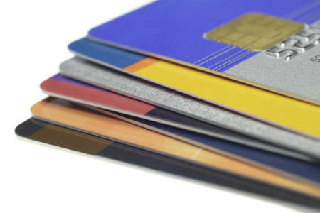 Many credit cards lie on one another on a white background
