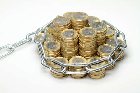 About 300 euro coins lying on a pile and be secured by a chain  photo