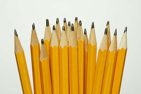 18 new yellow pencils on a light background