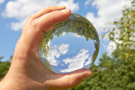 clairvoyant: In a held glass ball can you seen the landscape behind her  Stock Photo