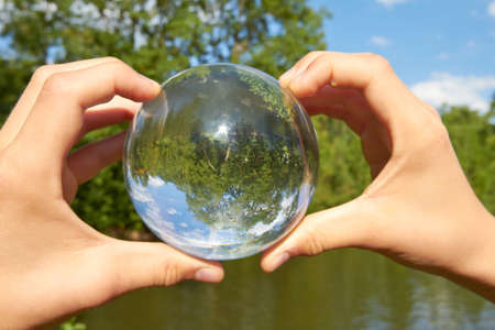 oracle: In a held glass ball can you seen the landscape behind her  Stock Photo