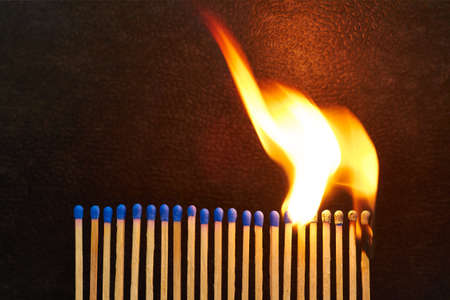 A series of matches are next to each other, which burn one after another  photo