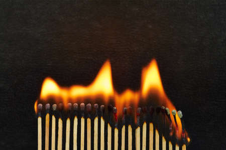 A series of matches are next to each other, which burn one after another Stock Photo - 22089060