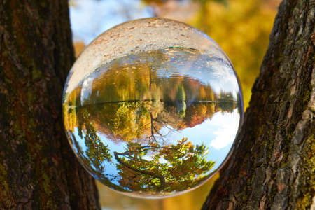 clairvoyant: In a glass ball can you seen the landscape behind her  Stock Photo