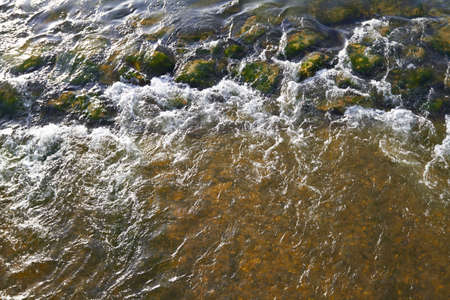 Rapid flowing water over rocks on a River  photo