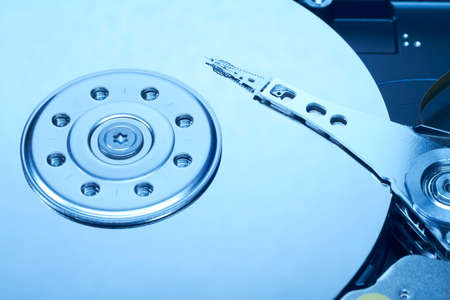 Close up of an opened hard disk with visible read head  photo