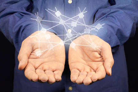 dataflow: A white network hovers above two hands.