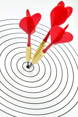 darts flying: A target has been hit by three darts in the center. Stock Photo