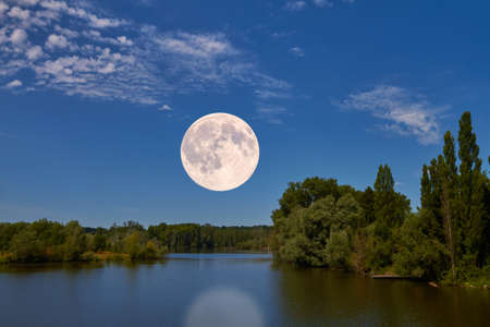 moon flower: The bright full moon hovers over an idyllic landscape. Stock Photo
