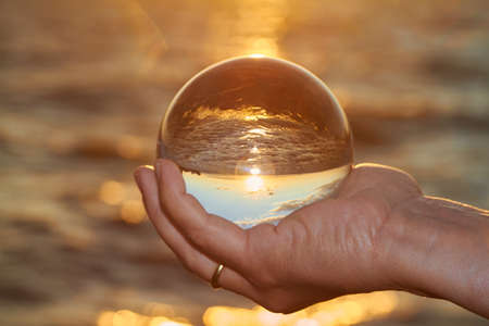 glass sphere: The sun sets over Lake Constance in Germany and lit by a crystal ball.