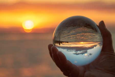 El sol se pone sobre el lago Constanza en Alemania y iluminados por una bola de cristal.