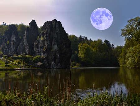 esoterismo: La luna brillante se cierne sobre una formación rocosa. Foto de archivo