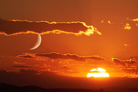 golden light: The sun and the moon can be seen in the sky Simultaneously. Stock Photo
