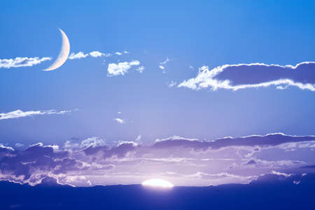 simultaneously: The sun and the moon can be seen in the sky Simultaneously. Stock Photo